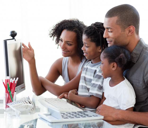 Família afro americana com um computador em casa